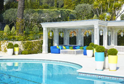 Lovely swimming pool and poolhouse with summer lounge sitting in a lush garden - Property Management